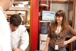 Meredith, my assistant, looks on as Paco, one of our editors/cooks, prepares food in our backup kitchen.