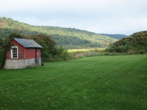 The milk house with fields and hills beyond.